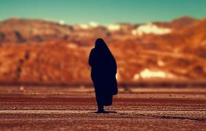 Mujer cubierta por un velo en un desierto de Oriente Medio (Unsplash).