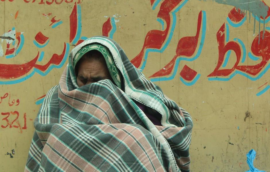 Mujer se cubre con una manta, procedente de Lahore (Pakistán).